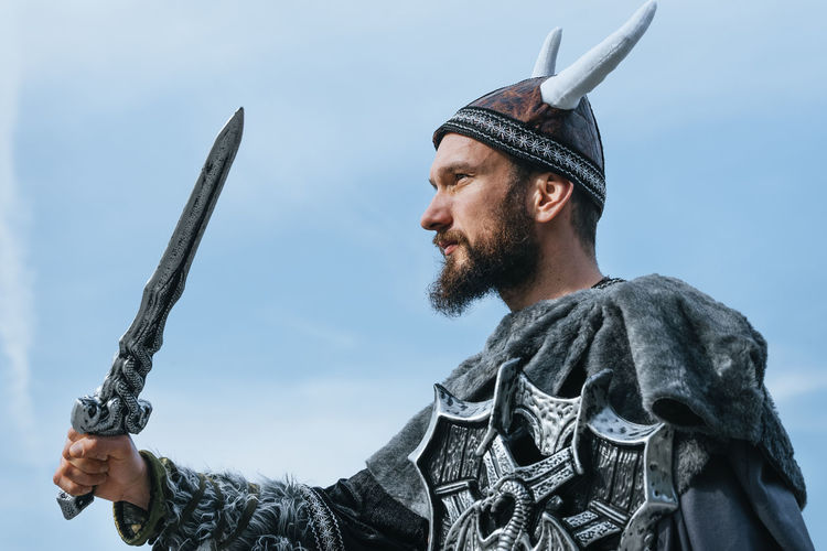 Low angle view of man in costume holding sword against sky