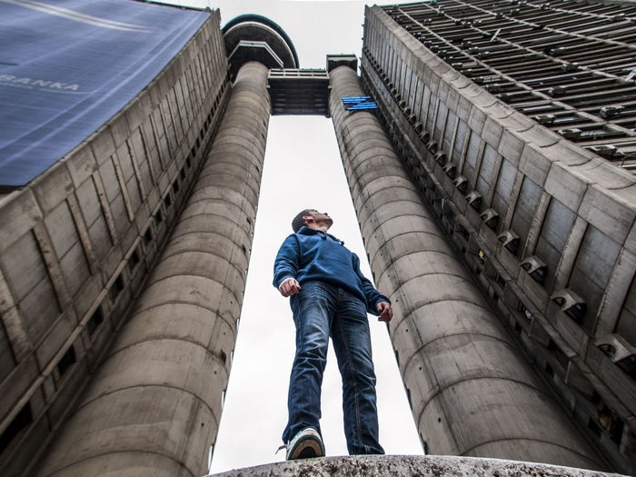 Low Angle View Of Man Standing Against Building