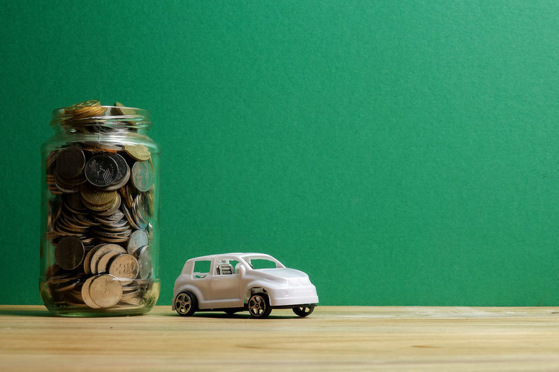 Auto Business Car Coin Colored Background Container Copy Space Finance Financing Green Color Indoors  Jar Large Group Of Objects Mode Of Transportation Motor Vehicle No People Responsibility Saving Savings Silver Colored Still Life Studio Shot Table Toy Wealth