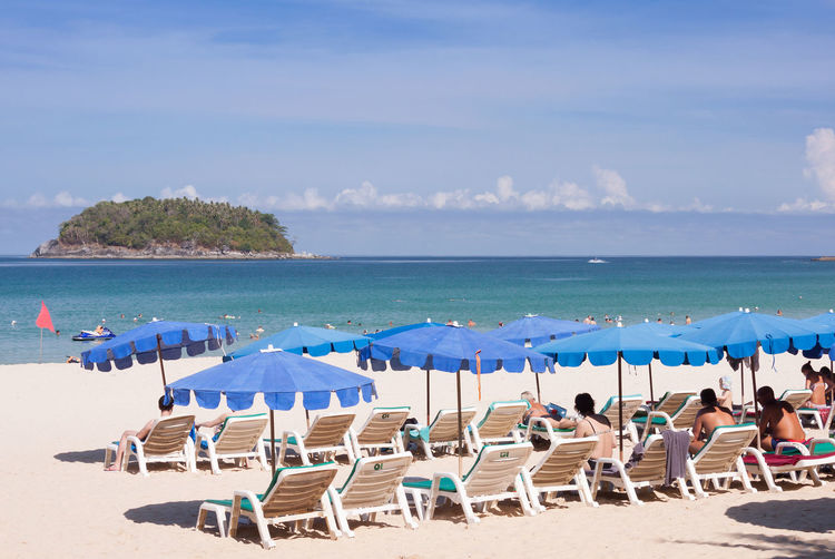 Lounge chairs and parasols on beach against sky