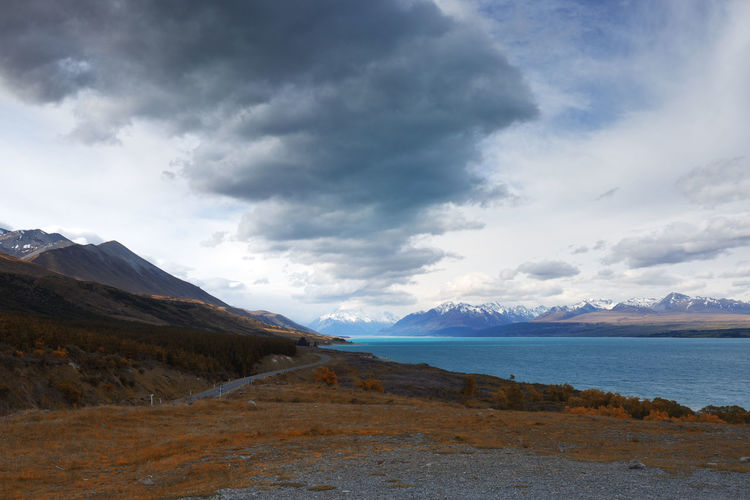 A view of country side road that passes through beautiful lake and mountains. Beauty In Nature Cloud - Sky Day Lake Landscape Landscape, Travel, People, Freedom, Mountain, View, Adventure, Journey, Tourism, Backpack, Trip, Nature, Hill, Tourist, Top, Snow, Outdoor, Beautiful, Clouds, Peak, Valley, Wanderlust, Lifestyle, Explore, Scenic, Lake, Relaxing, Leisure, Sky, Mountains, M Mountain Mountain Range Nature No People Outdoors Range Scenery Scenics Sky Tranquil Scene Tranquility Water
