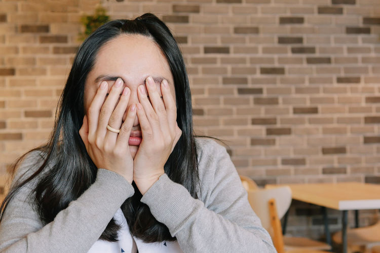 Portrait of a woman covering face