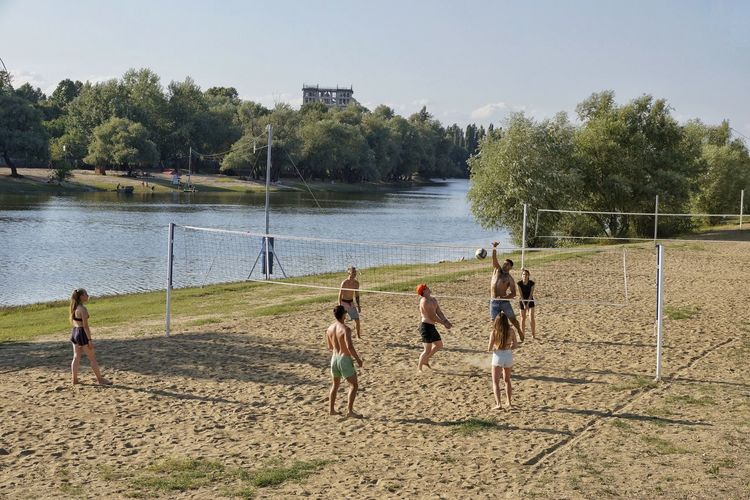 Friends playing volleyball on sand by lake against sky