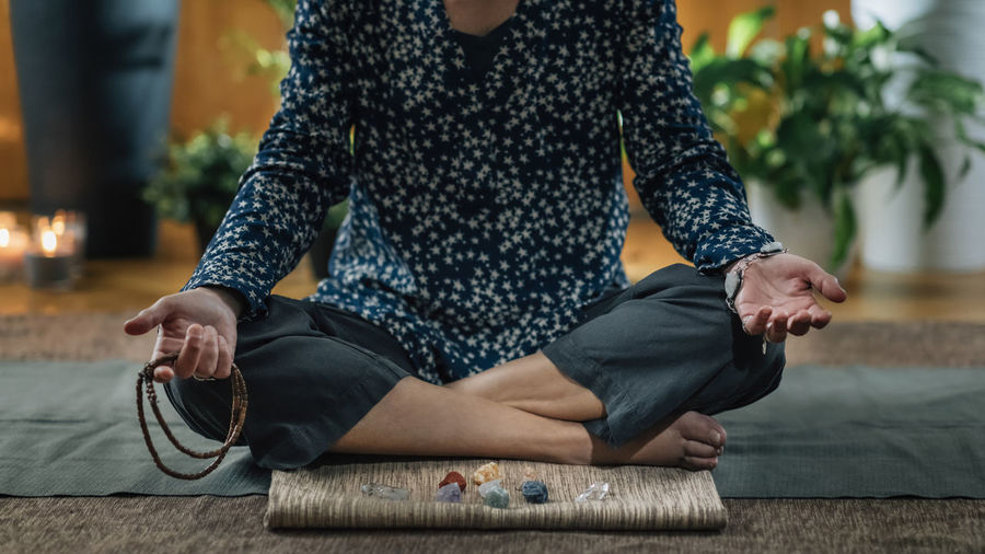Low section of woman meditating at home