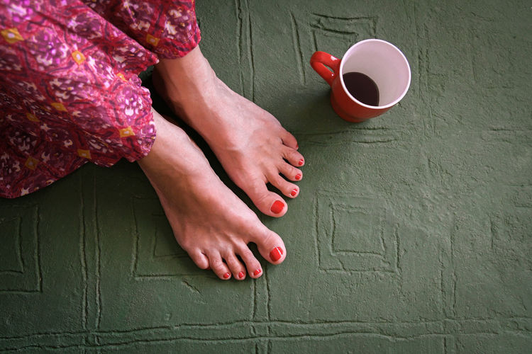 Close up view of barefoot woman with red nails colorful hippie style skirt and a cup of coffee. Top view of trendy girl sitting on green vintage decorated floor. Relax, female intimacy, healt concept. Above Alone Attractive Background Batik Beautiful Beauty Body Care Casual Caucasian Color Comfort Cute Design Easy Feet Finger Foot Fun Green Healthy Holiday Indoors  Interior Lady Legs Leisure Lifestyle Living Modern Nature One Pedicure People person Portrait Pose Posing Pretty Relaxed Resting Room Sit Sitting Spa Travel Vacation Young