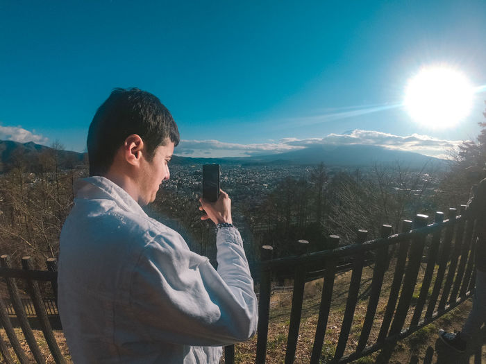Man photographing while standing by railing against sky