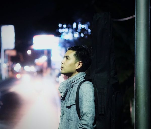 Thoughtful man standing at illuminated city street during night