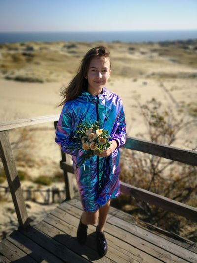 Portrait of girl holding bouquet while standing at beach