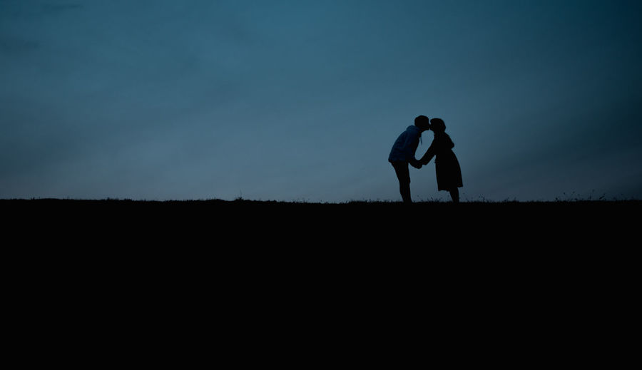 Silhouette Couple Kissing On Landscape Against Sky During Sunset