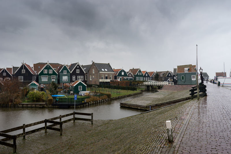 Houses By River Against Buildings In City