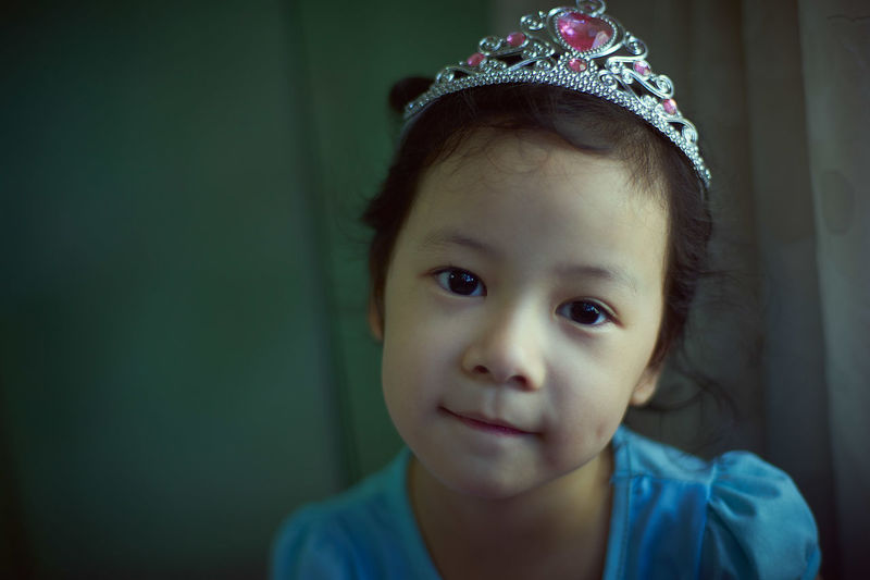 Portrait Of Girl Wearing Crown While Sitting At Home