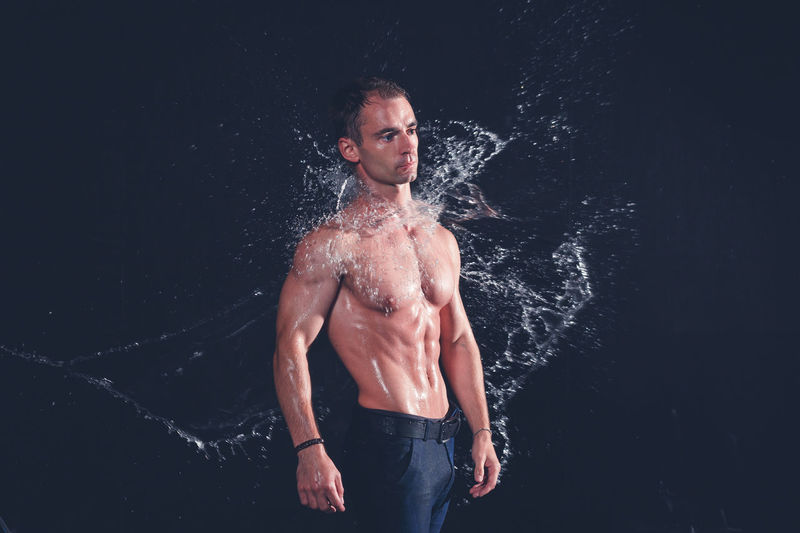 Shirtless man standing against black background