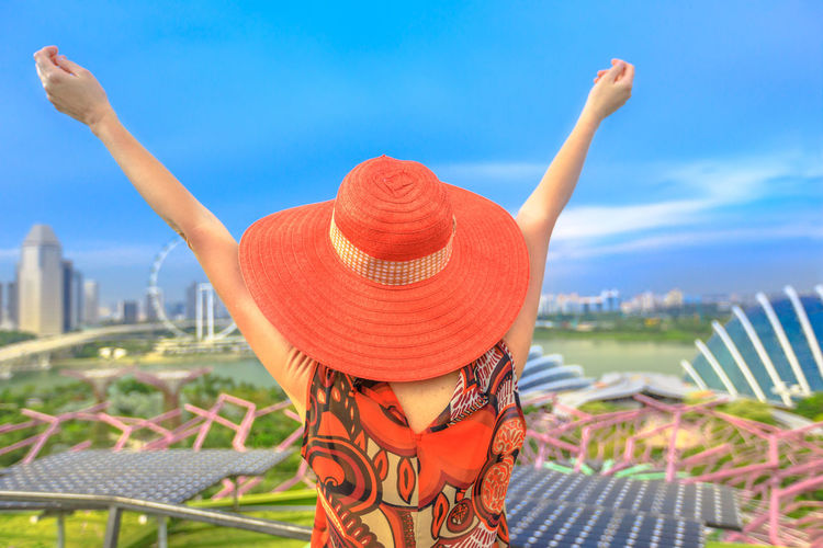 Happy woman in res hat and with open arms enjoying cityscape of Singapore. Blonde tourist above aerial view of Singapore marina. Travel holiday vacation in Singapore, Southeast Asia,Sunny day blue sky Singapore Singapore City Woman Tourist Tourist Attraction  Tourist Destination People Girl Females Aerial View Skyline Cityscape Panorama Happy Travel Hat Lifestyle Enjoy Nature Tourism Sky One Person Focus On Foreground Architecture Real People Building Exterior Human Arm Lifestyles Leisure Activity Built Structure Rear View Arms Raised Day Red Orange Color Women Cloud - Sky Clothing Outdoors
