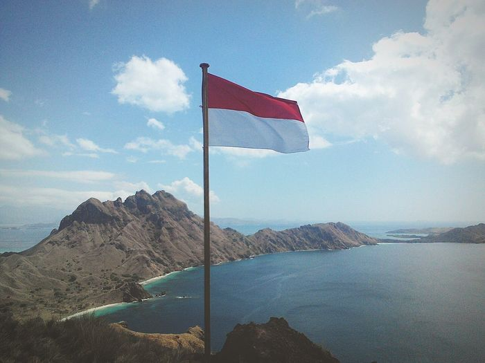 Indonesian flag waving on cliff with sea in background against blue sky