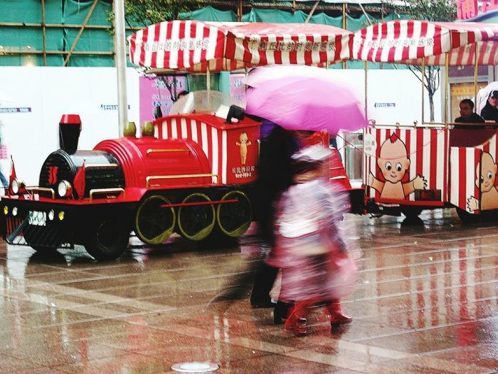 capturing motion Red Outdoors Real People Day People Blurred Motion Blurred Eyeemphoto From My Point Of View Raining Umbrellas Brollies Blurry Wet Days Streetshots Trainrides Parenthood Parentandchild Love Blurred On Purpose Rainy Days Rain Rainy Day Photography Kiddy Ride The Street Photographer - 2017 EyeEm Awards