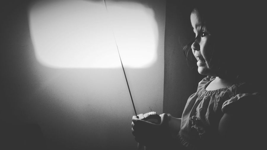 Side view of girl holding measuring tape on illuminated electric lamp