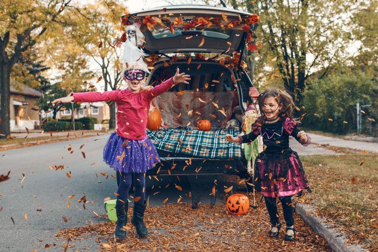 Trick or trunk. children siblings sisters celebrating halloween in trunk of car. friends kids
