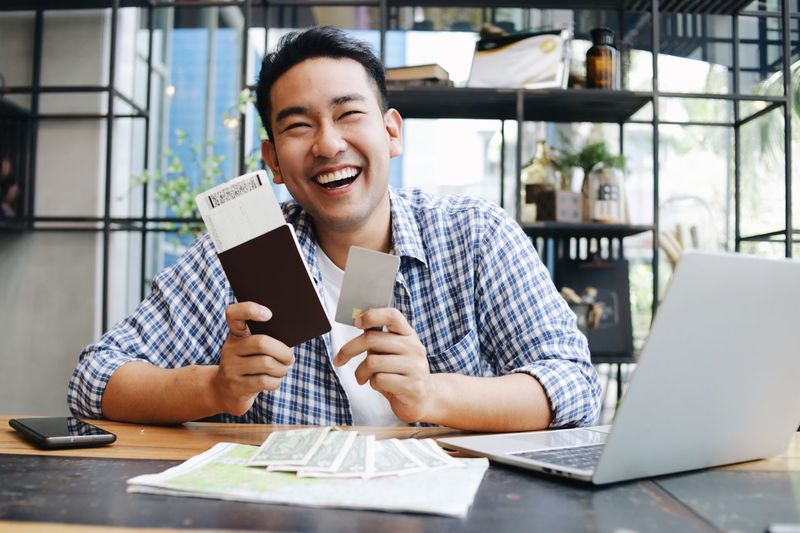 Man holding passport while sitting at home