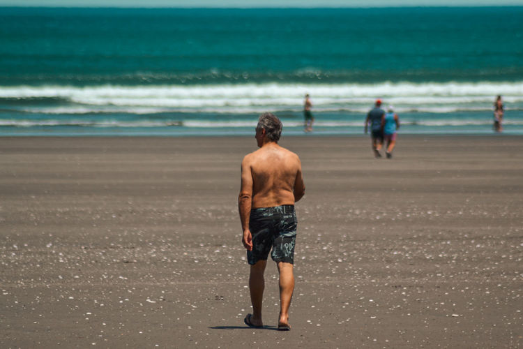 Rear view of shirtless man walking on beach