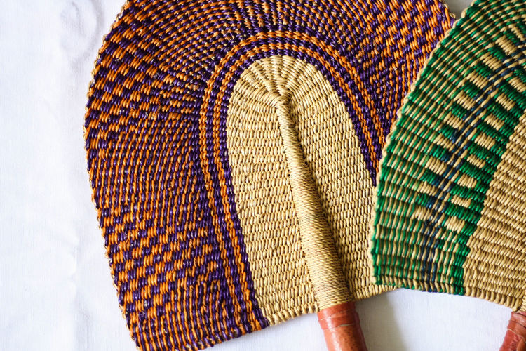 Handmade, hand weaved Bolga fans with leather warped handle from Dakar, Senegal. African Dakar Green Green Color Leather Orange Basket Weave Close-up Day Fan Handmade Home Decor Indoors  Items Leather Craft Multi Colored No People Pattern Senegal Still Life Tan Weaving