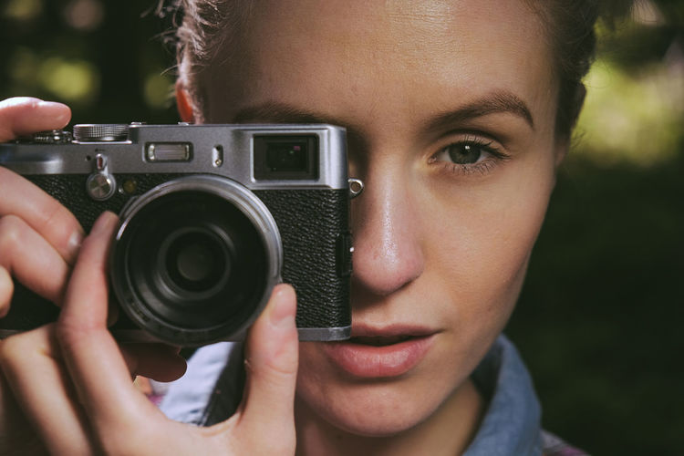 portrait of a young caucasian woman looking through a vintage camera viewfinder Artist Camera Camera - Photographic Equipment Caucasian Holding A Cat Nature One Person Outdoors Outside People Photographer Photographing Photography Themes Portrait Retro Vintage Woman Young Adult