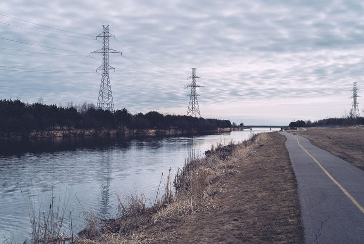 Empty road by river against cloudy sky