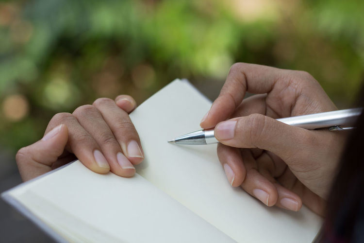 Close-up of man holding paper with hand on table