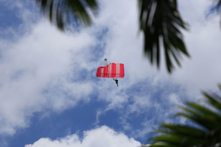 Low Angle View Of Person Flying With Parachute In Sky