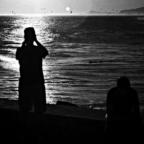 Silhouette people standing on beach at sunset