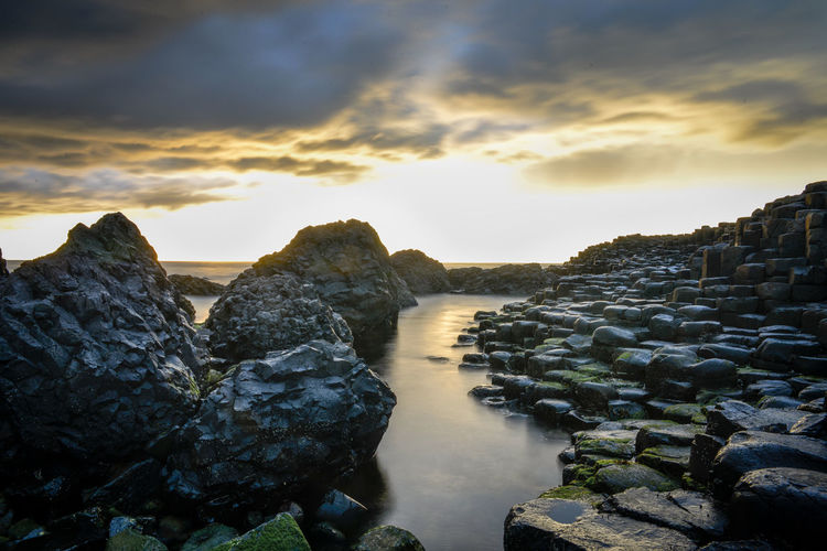 Rocks in sea against sky during sunset