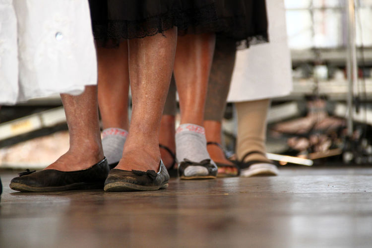Low section of women wearing shoes standing on floor