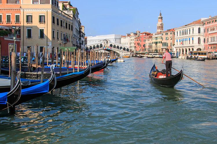 Rear view of man sailing gondola over grand canal against rialto bridge
