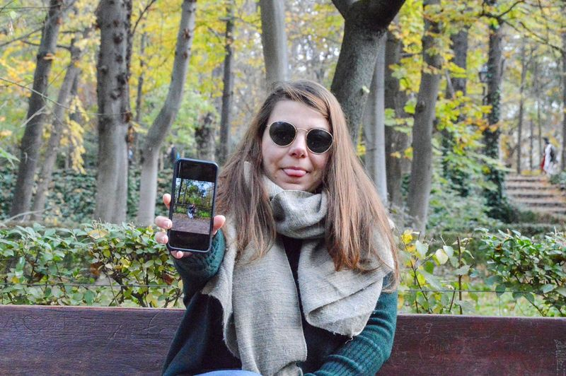 Portrait of woman showing mobile phone in forest