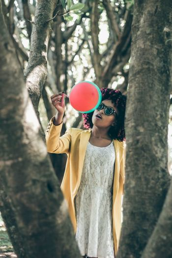 Young woman holding balloon by tree