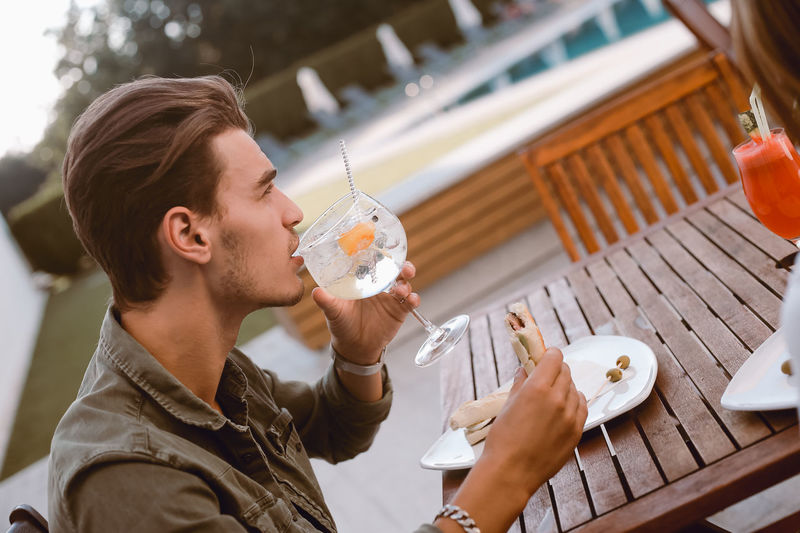 Midsection of man drinking glass on table