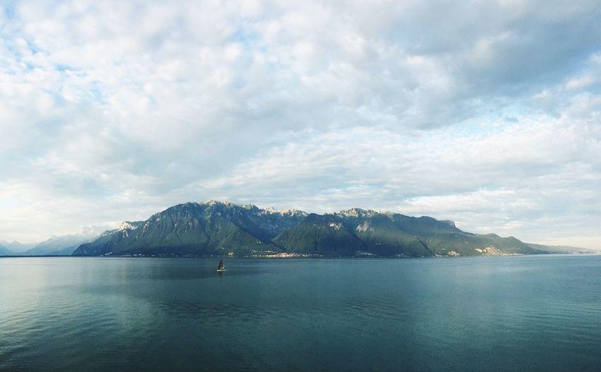Idyllic shot of lake and mountain range against cloudy sky