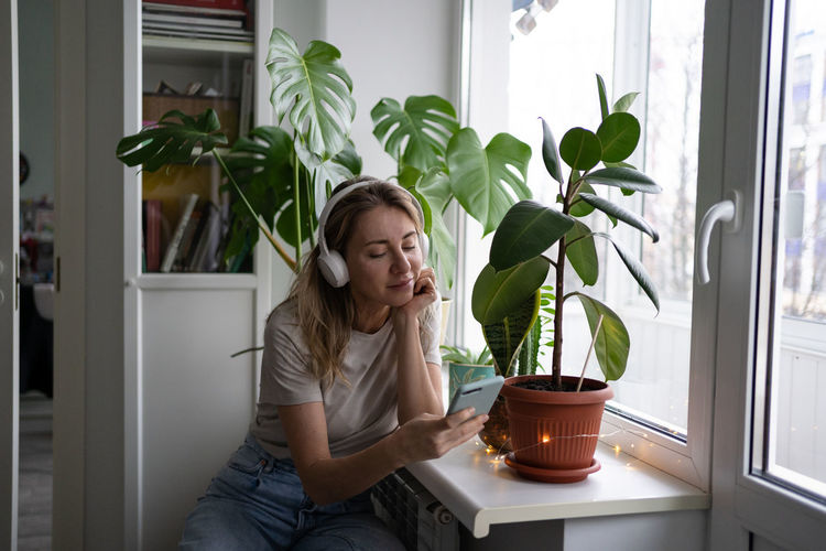 Young woman sitting on potted plant at home