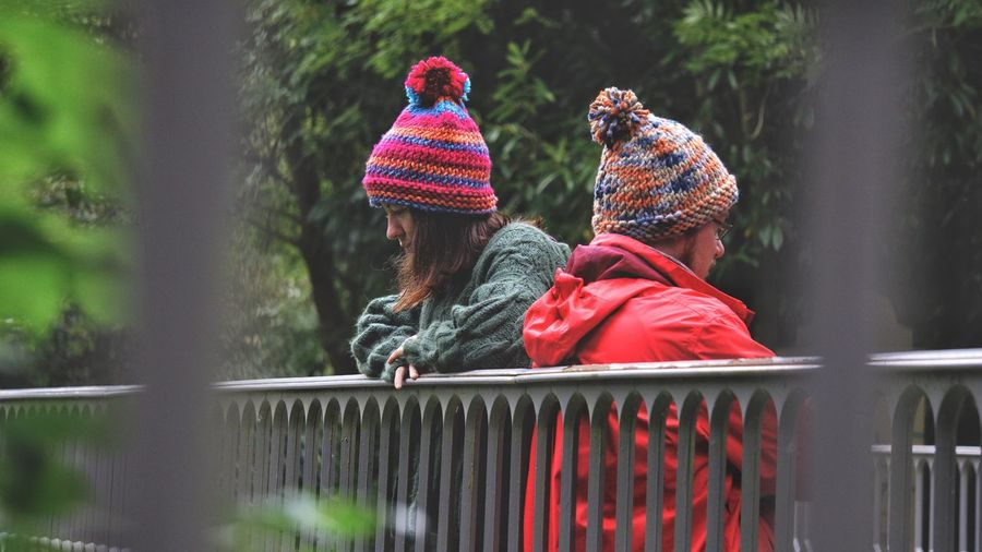 Friends Wearing Knit Hats By Railing At Park