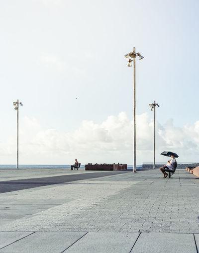 Man Sitting On Promenade At Beach Against Sky