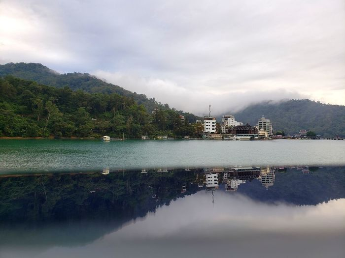 Reflection of buildings and trees in water against sky