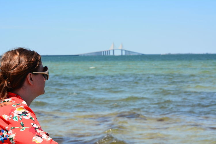 Side view of woman against sunshine skyway bridge over tampa bay