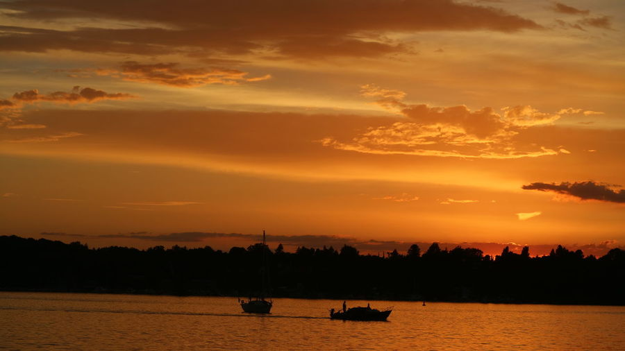 Silhouette Boat Sailing On River Against Dramatic Sky During Sunset