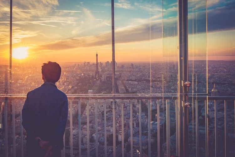 Rear view of man standing by cityscape against sky during sunset