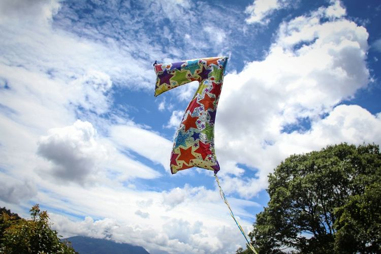 Low angle view of colorful number 7 helium balloon against cloudy sky