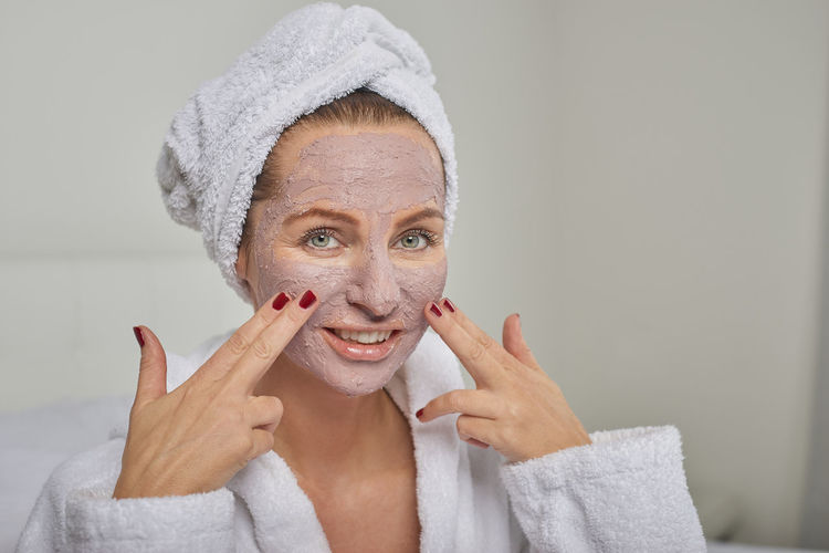 Woman at a spa with a face mask Woman Applying Beautiful Woman Beauty Beauty Mask Beauty Treatment Best Ager Body Care Clay Face Face Mask Happiness Health Spa Lifestyles Looking At Camera Middle-aged Portrait Spa Treatment Towel Wellbeing