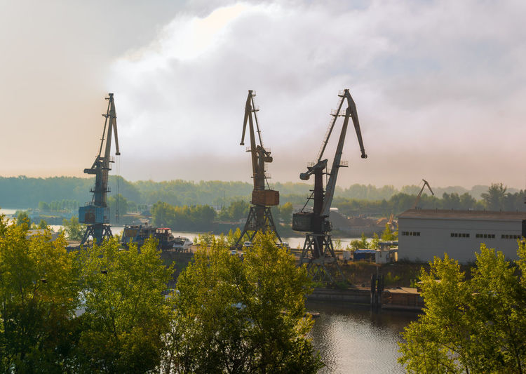 Commercial dock by river against sky
