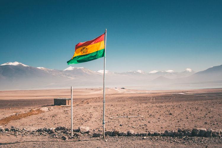 Bolivian flag fluttering on landscape against clear sky