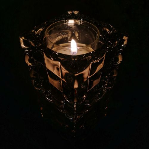 A candle in a glass. Candle Glass Reflection Black Background Illuminated Electricity  Flame Filament Lighting Equipment Close-up Darkroom Candlestick Holder Fire - Natural Phenomenon Candlelight Burning Fire Lit