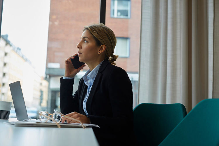 Rear view of woman using mobile phone at table
