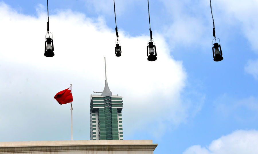 The twin towers of the Bahrain Financial Harbour as seen from the Manama Suq Bahrain Financial Harbour Architecture Building Building Exterior Built Structure City Cloud - Sky Day Decoration Flag Hanging Lighting Equipment Low Angle View Nature No People Outdoors Patriotism Red Sky Spire  Tower
